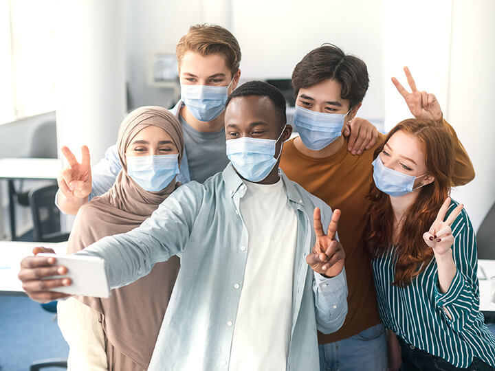 International students wearing medical face masks taking selfie
